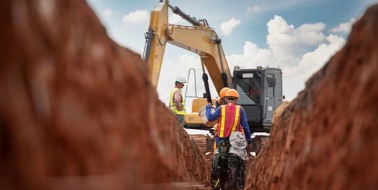 construction workers standing inside a trench with an excavator in the background