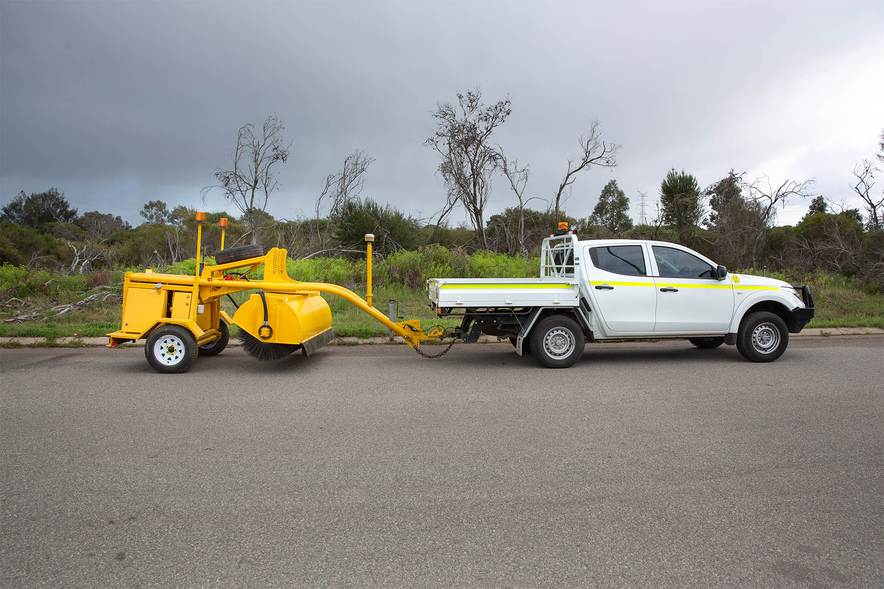 road sweeper mounted to the back of a ute
